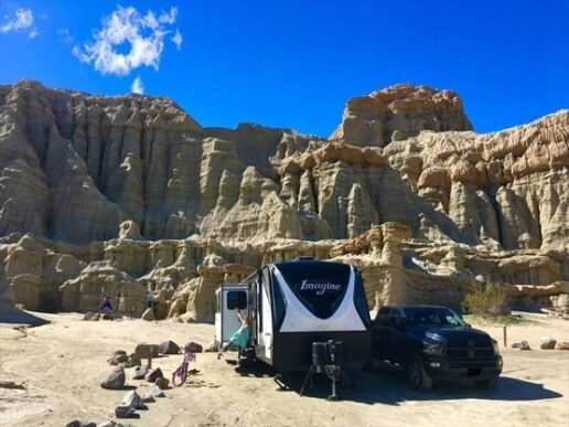 Campers outside their travel trailer near a rock formation in the American southwest