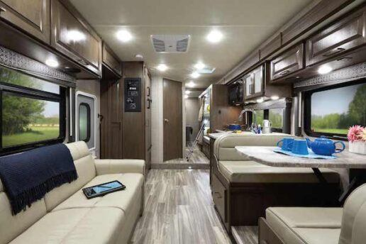 A picture of the interior of Thor Motor Coach's 2021 Fourwinds 31E. The picture shows a sofa on the left and a dinette on the right. Cabinetry above the furniture is a grayish brown.