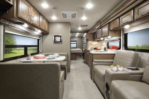A picture inside a 2021 Magnitude Omni SV34. The photo shows a tan/gray dinette on the left and similarly colored recliners on the right. Grayish brown cabinets line the ceiling on both sides of the motorhome.