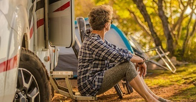 woman sitting next to an RV at campground