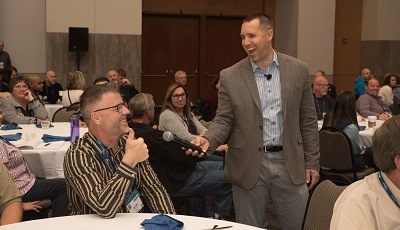 A picture of Kyle Sanders of SEEK More Solutions laughing with an OHCE2019 attendee during the Opening General Session of last year's event in Nashville, Tenn.