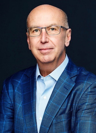 A head and shoulders picture of OmniMax International CEO John C. Wayne