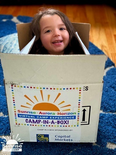 """A picture of a Care Camps kid in a """"Camp in a Box"""" package"""