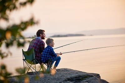 A picture of a father and son fishing near a lake