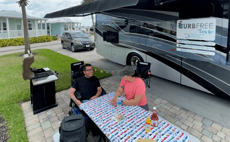 A picture of Cory Woodard and his family sitting outside the Winnebago Inspire AE unit
