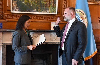 A picture of Tommy Beaudreau being sworn in by Deb Haaland
