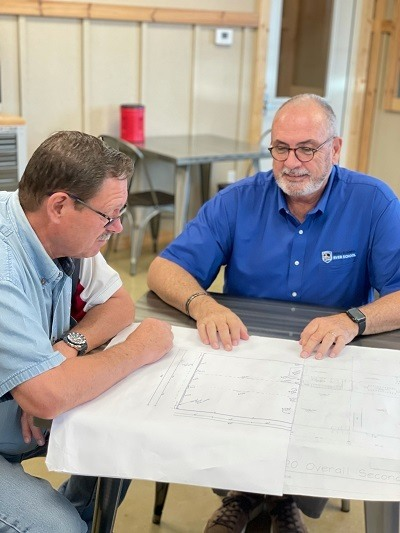 A picture of NRVTA Terry Cooper and Steve Anderson looking at building expanson plans