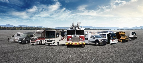 A stock photo of all the specialty vehicles made by Rev Group on an asphalt area with mountains in the background