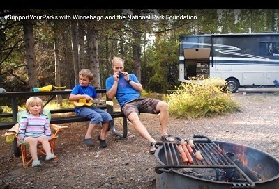 A screenshot of Winnebago's video promoting its National Parks contest song. The picture has a father and two young children sitting at a campfire with a Winnebago Type A motorhome in the background