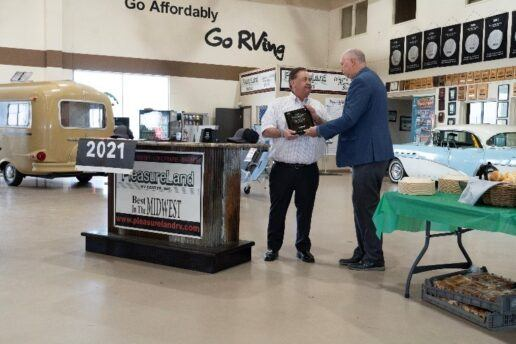 A picture of PleasureLand RV recieving a Flying W award for the 38th year
