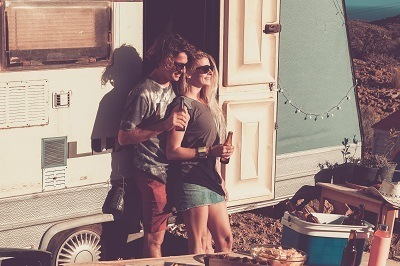 A picture of a millennial couple camping with an RV