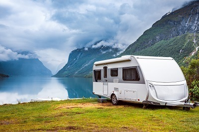A picture of a general travel trailer parked by a lake