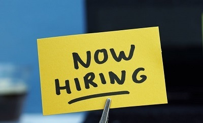 A picture of Now Hiring written on a sticky note, held by tweezers