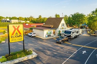 A picture of the entrance to a KOA campground, with a pickup hauling a Keystone RV Cougar fifth wheel