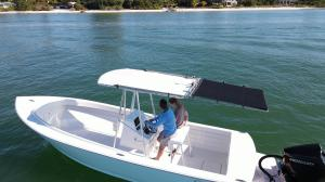 A picture of the Lippert SureShade PTX Power Shade covering a pair of boaters in their powerboat