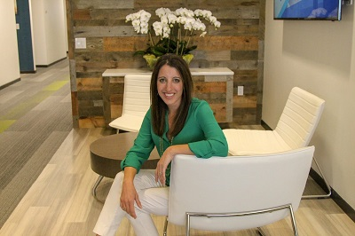 A picture of Trader Interactive CEO Lori Stacy sitting in a white chair