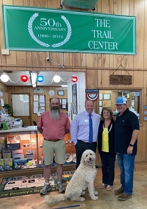 A picture of Pete's RV owners posing with The Trail Center owners after Pete's RV Center bought the dealership