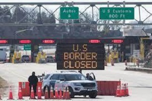 A picture of the US Canada border with an electric sign reading U.S. Border Closed