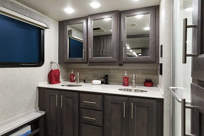 A picture of the dual vanity bathroom in an upgraded en suite within the 2022 Thor Motor Coach Aria 3901