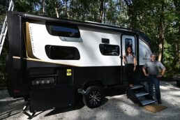Ember RV President and CEO Ashley Bontrager and Vice President Chris Barth stand outside the exterior of a 2022 prototype RV