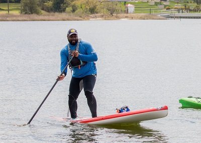 A picture of Together Outdoors Lead Gerry Seavo James standing on a small floatation device with a paddle in his hand