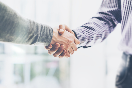 A picture of two people shaking hands on an agreement or deal