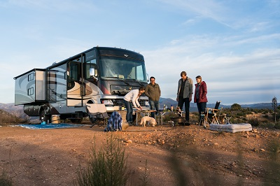 A picture of four people outside a Type A motorhome cooking outdoors
